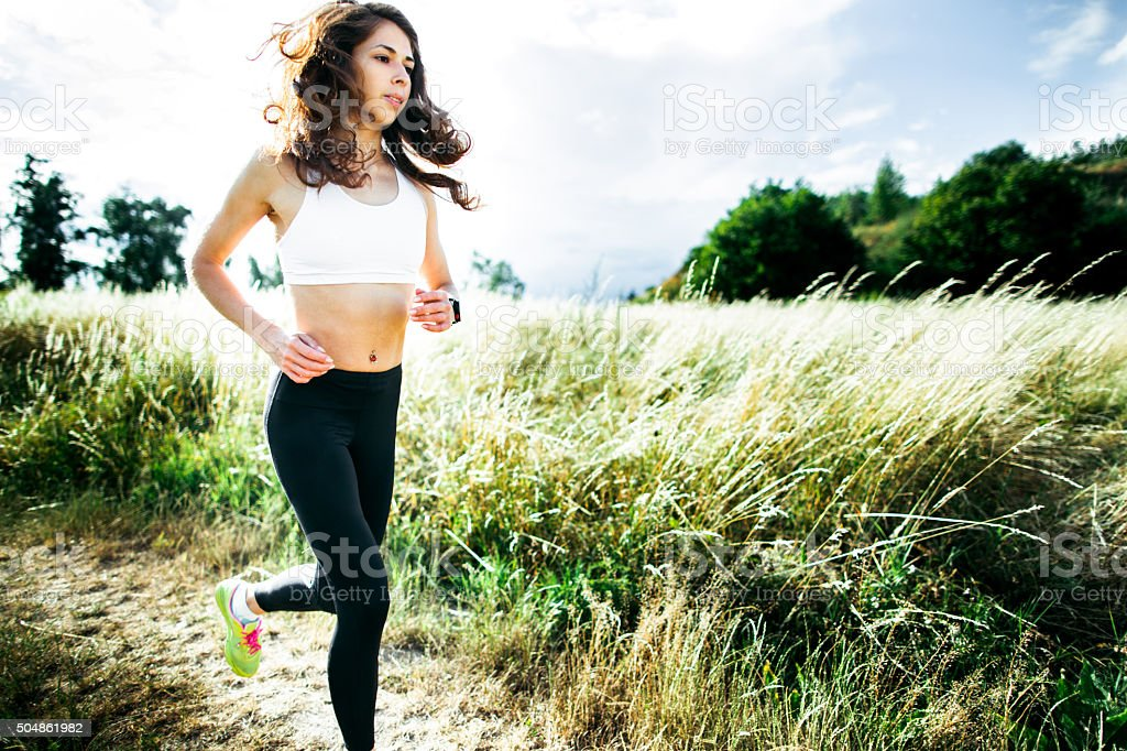 Young woman running through the field stock photo