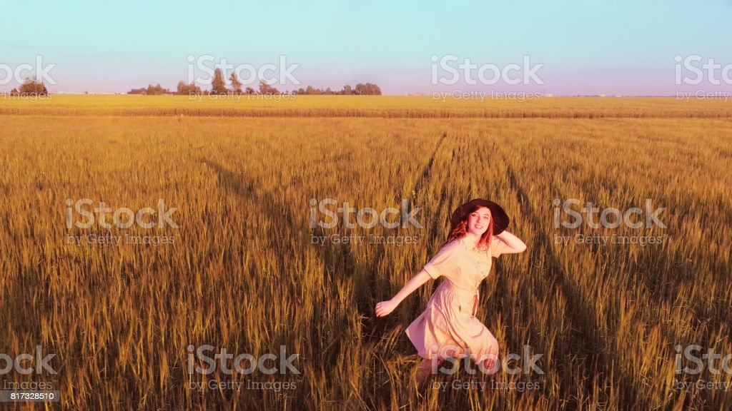 Young Woman Running Through Wheat Field stock photo