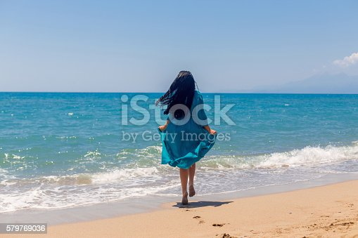 istock Young woman runnnig on the beach 579769036