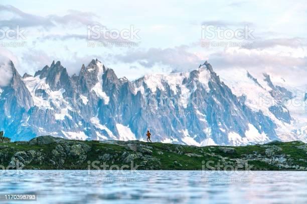 Photo of Young woman runs along lake below mountains