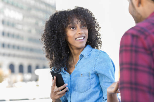 Young woman runs into old friend on city street A surprised young woman pauses from texting on her smart phone to greet an unrecognizable old friend on a city street. stranger stock pictures, royalty-free photos & images