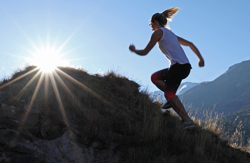 istock Young woman runs to the top of a knoll at sunrise 1153861054