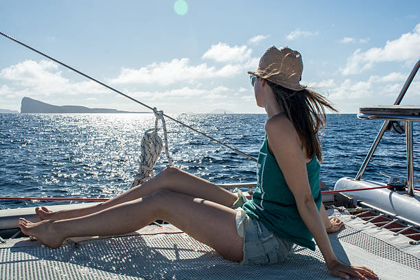 Young woman sailing on catamaran in the sun stock photo