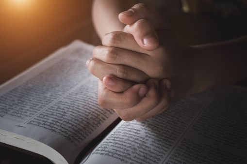 A young woman sat and studied the scriptures laid on a wooden table. The educational concept of the Christian Tripitaka that is open and praying to God Faith in the divine power of God. Bible study.