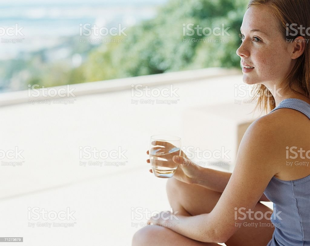 Young woman sat outdoors with glass of water royalty-free stock photo