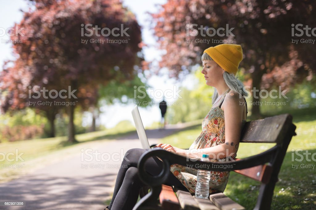 Young woman sat using her laptop in the park royalty-free stock photo