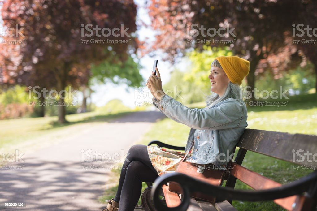 Young woman sat using her phone in the park royalty-free stock photo