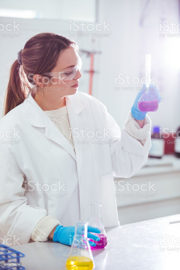 young woman scientist working with laboratory glassware with different colors liquid in a laboratory stock photo
