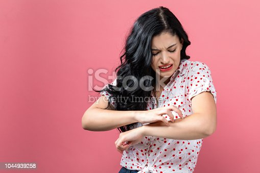 istock Young woman scratching her itchy arm. 1044939258