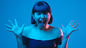 istock Young woman scream yell isolated on blue neon copyspace 1303517585