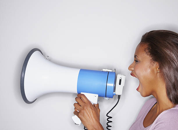 Young woman screaming into a bullhorn stock photo