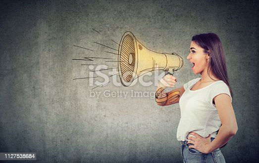 910149000istockphoto Young woman screaming into loudspeaker 1127538684