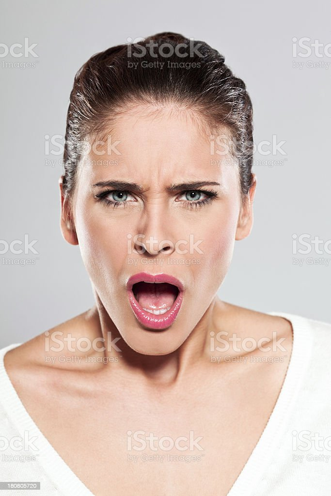 Young woman screaming, Studio Portrait Portrait of young woman screaming at the camera. Studio shot on a grey background. 20-24 Years Stock Photo