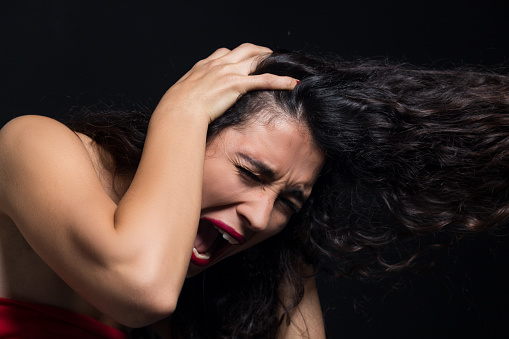 487960859 istock photo A young woman screaming uncontrollably while isolated on a black background 1184914622