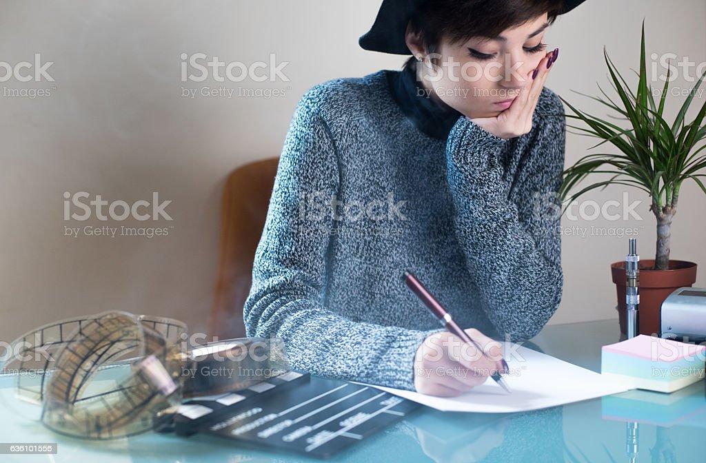Young woman screenwriter working desktop stock photo
