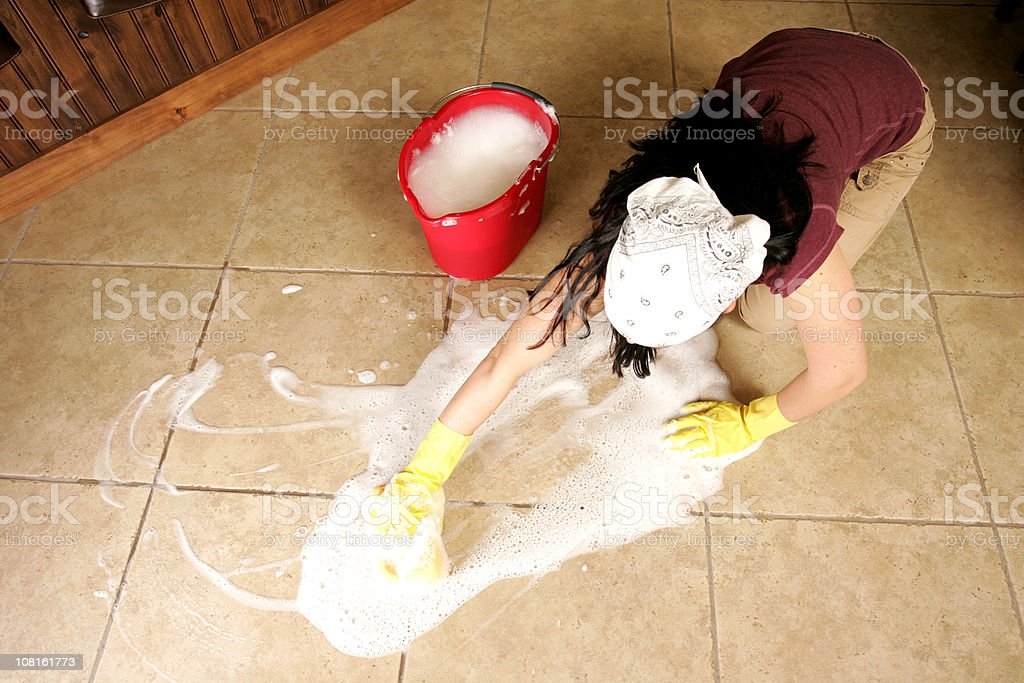 Young Woman Scrubbing Tile Floor Beside Bucket royalty-free stock photo