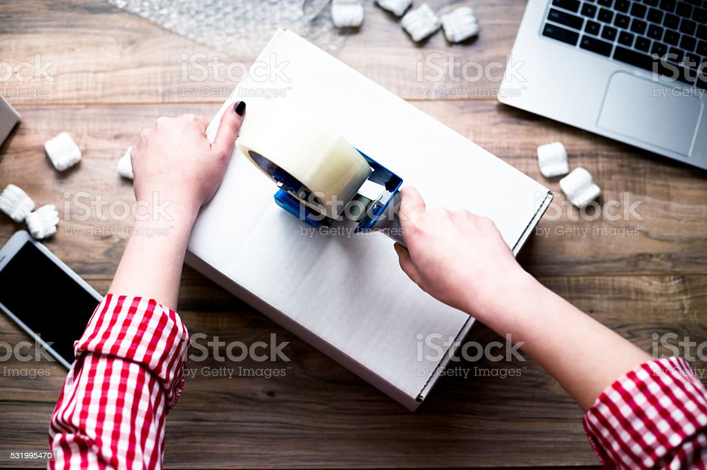 Young woman sealing a box with tape. stock photo