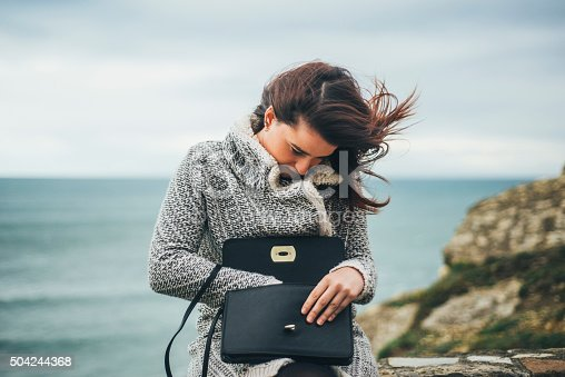 A young woman checks her purse trying to find something inside it.