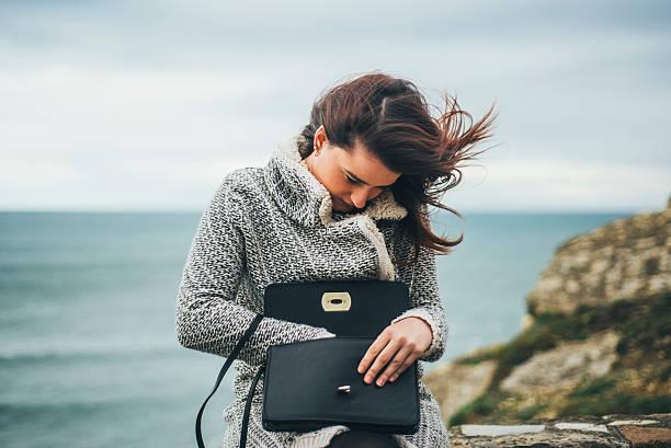 junge frau auf der suche in ihrer tasche - leder handtaschen damen stock-fotos und bilder