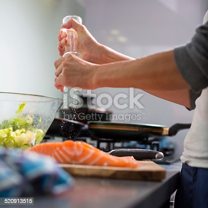 Young woman seasoning a salmon filet in her modern kitchen, prepaaring a healthy food