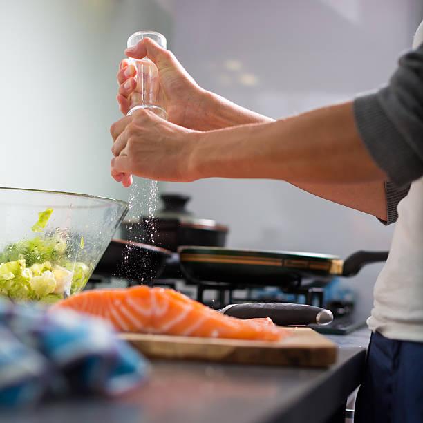 young woman seasoning a salmon filet - flat cap stockfoto's en -beelden