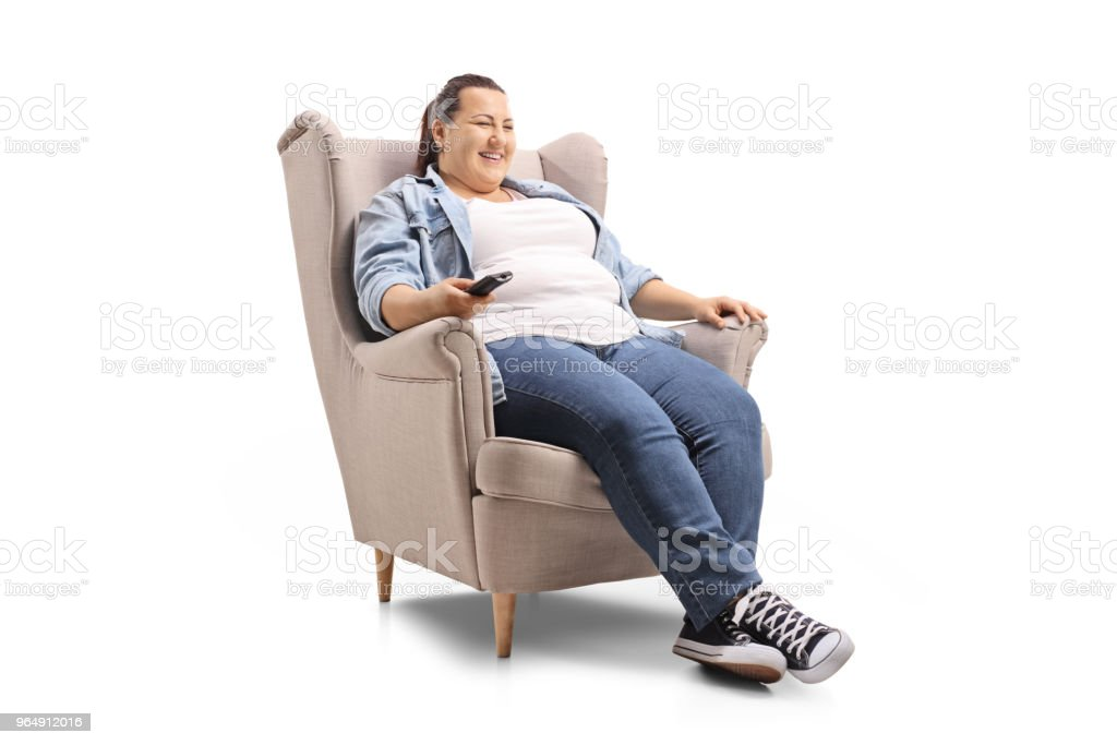 Young woman seated in an armchair watching television and smiling royalty-free stock photo