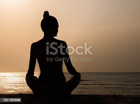istock Young woman seating in the lotus position on the beach against sunset. Yoga and meditation concept 1091383596