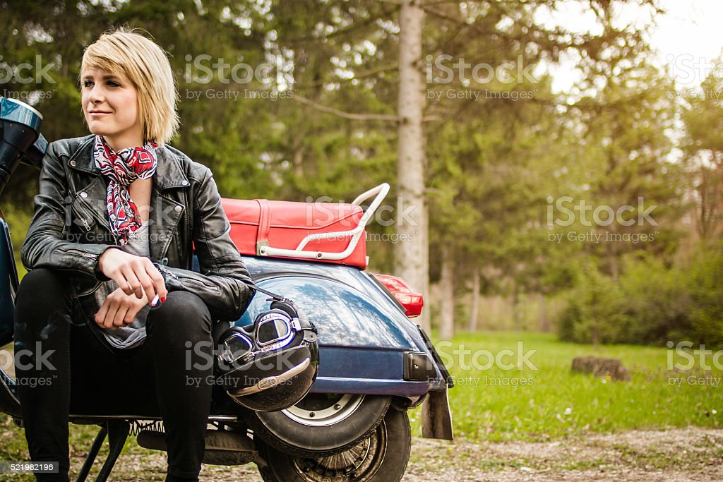 Young woman seating on a scooter motorcycle stock photo