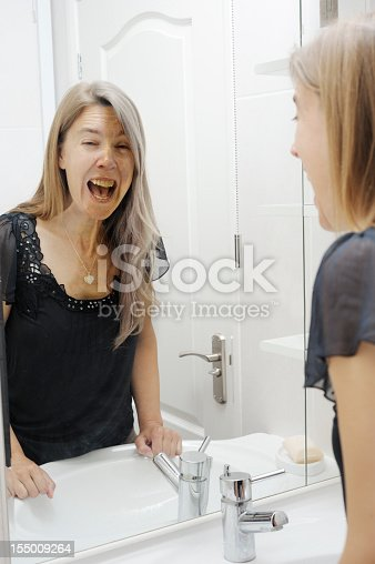 661896674istockphoto Young woman sees ageing mirror image 155009264