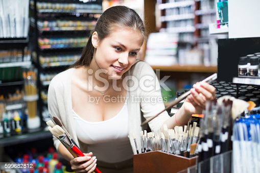 594918592 istock photo young woman selecting brushes in shop 599682812