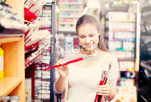 594918592 istock photo young woman selecting brushes in shop 628811132