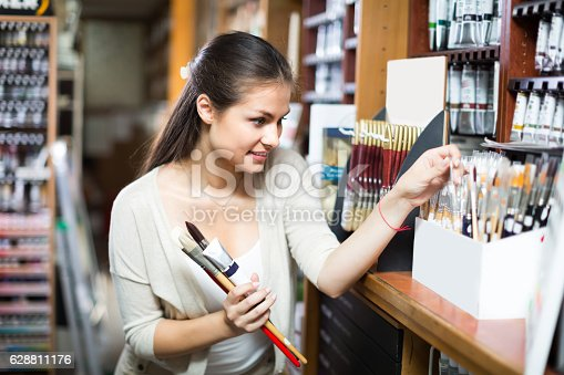 594918592 istock photo young woman selecting brushes in shop 628811176