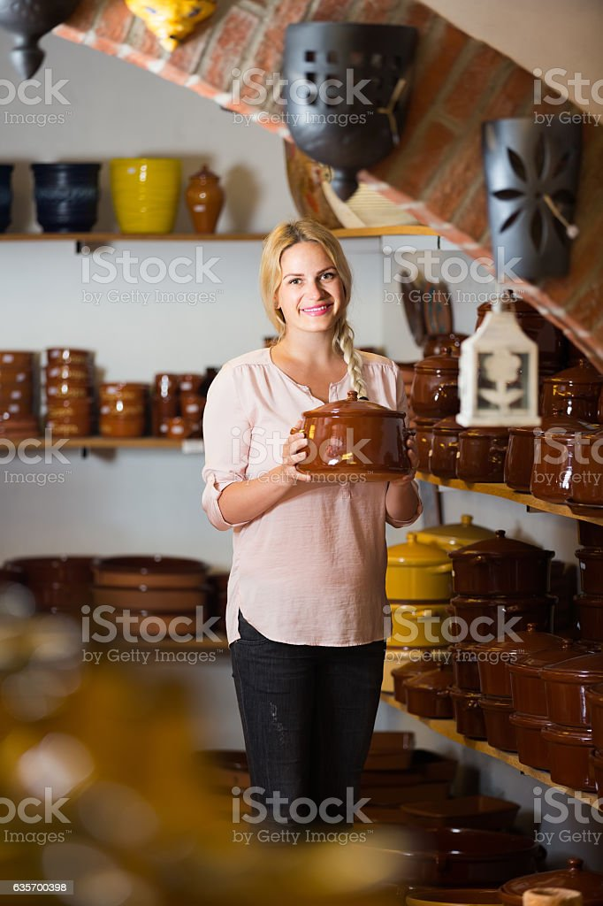 young woman selecting ceramic dish ware in atelier royalty-free stock photo
