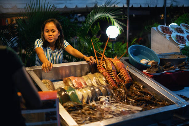 Young woman sell seafood on street market, Philippines. stock photo