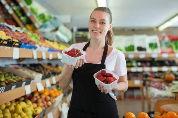 Junge Verkäuferin steht mit kleinen Kisten Erdbeere – Foto