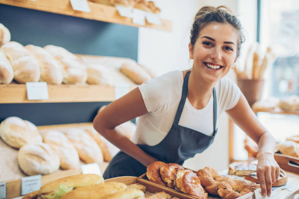 Young woman selling bread and pastry stock photo
