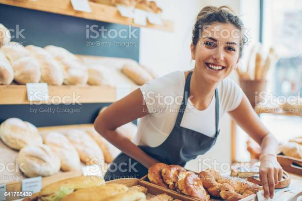 Smiling young woman selling bread in the bakery