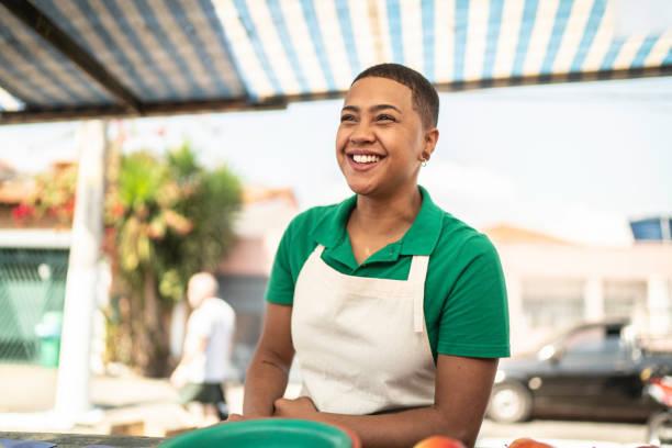giovane donna che vende frutta a un cliente in un mercato di strada - bancarella foto e immagini stock