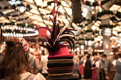 Munich, Germany - September 21, 2019: young woman selling colorful traditional hats to the guest of Oktoberfest