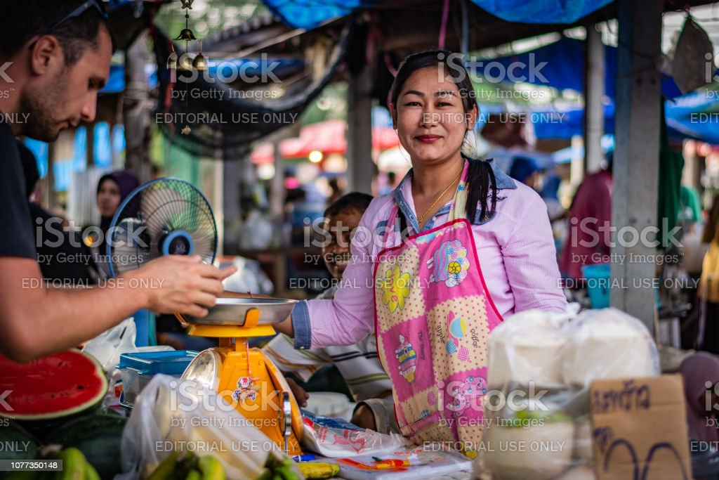 Young woman sells fruit at a market on the island of Koh Lanta, a woman accepts payment from a man, between them stands a weight, Thailand – zdjęcie