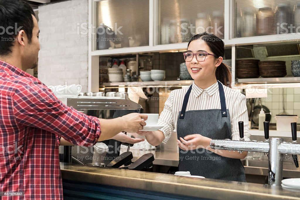 Young woman serving coffee to male customer stock photo