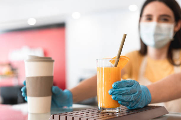 Young woman serving fresh orange juice and takeaway coffee inside bakery cafeteria while wearing safety mask and gloves for coronavirus spread prevention - Main focus on right hand stock photo