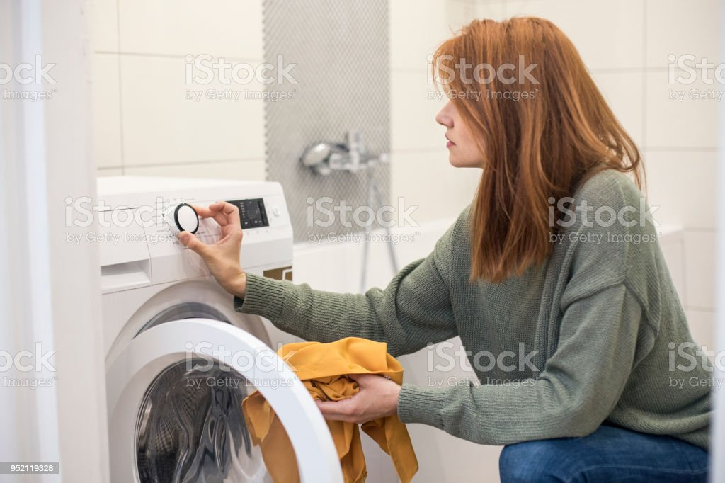 Young woman setting a washing machine stock photo