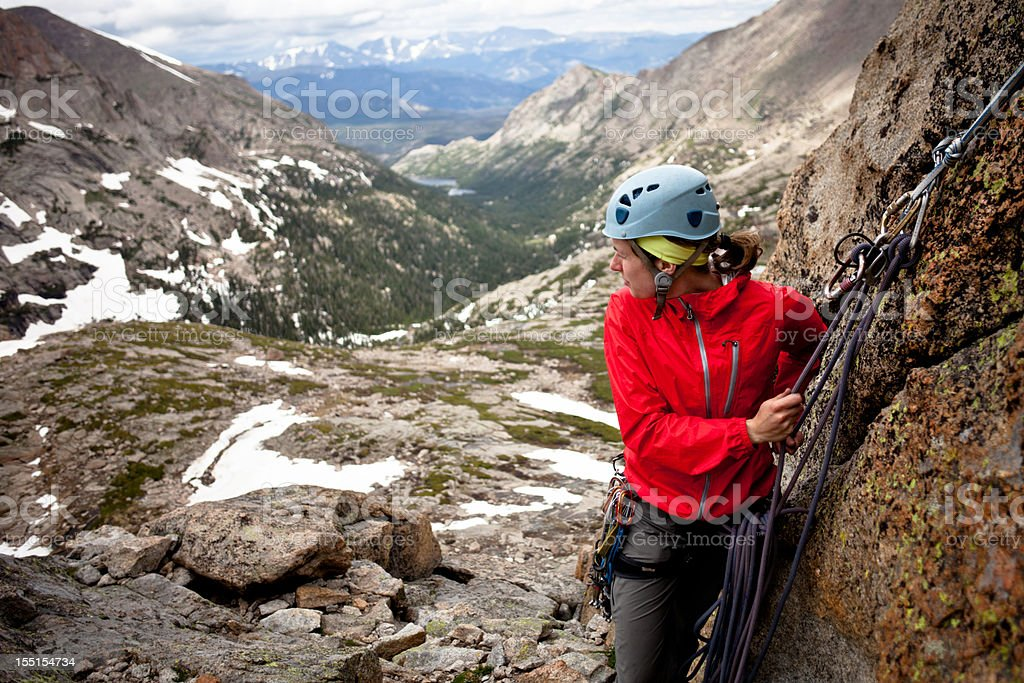 Young woman setting an anchor and belaying her partner stock photo