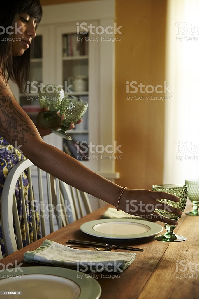 Young woman setting table royalty free stockfoto