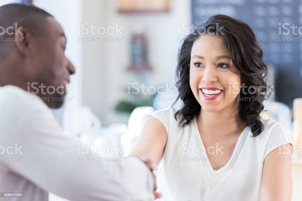 Young woman shakes hands with unrecognizable man in coffee shop stock photo