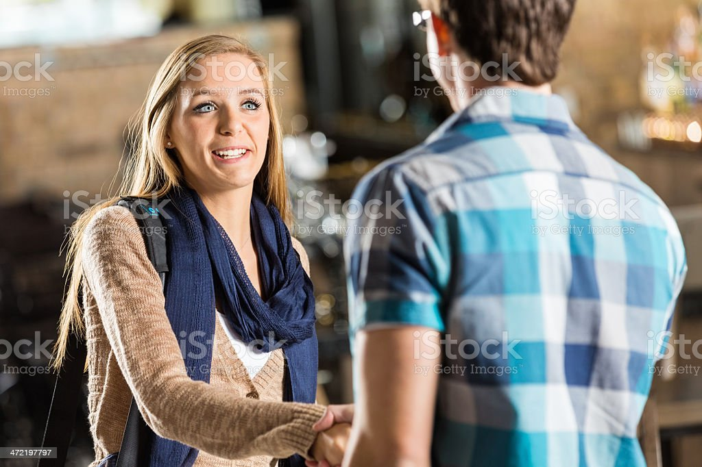 Young woman shaking hands with friend in coffee shop stock photo