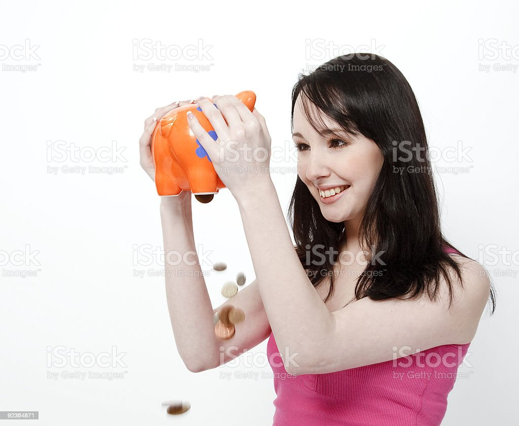 Young woman shaking money from piggy bank royalty-free stock photo