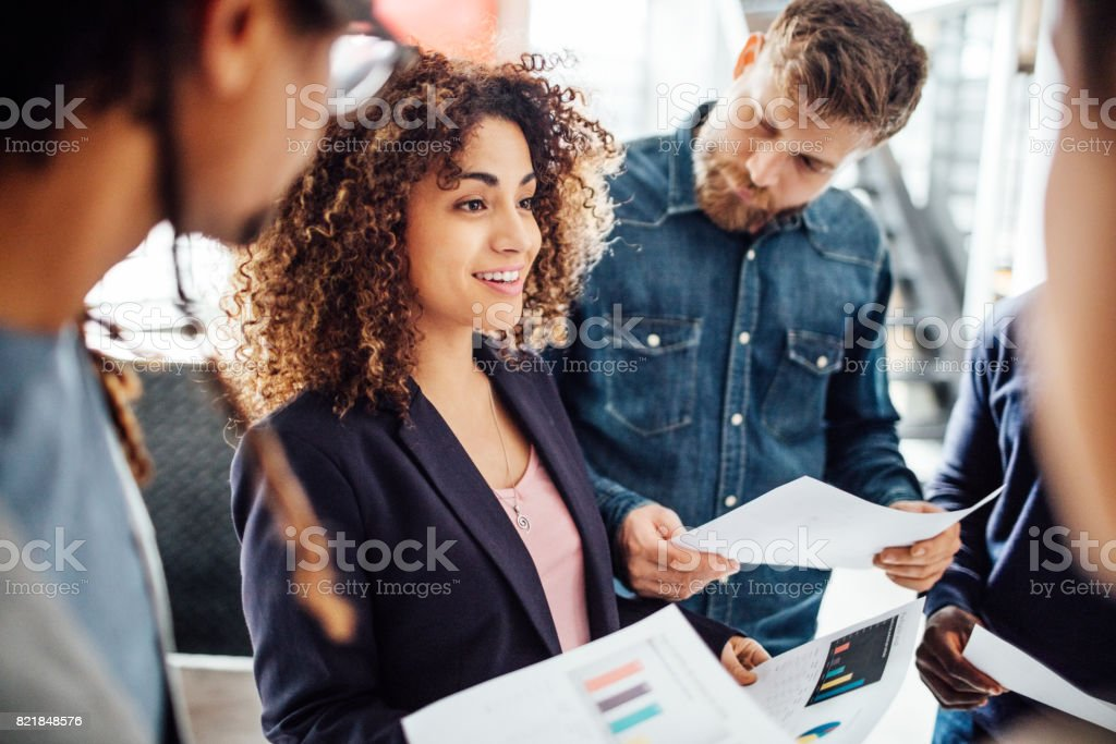 Young woman sharing business reports with colleagues. stock photo
