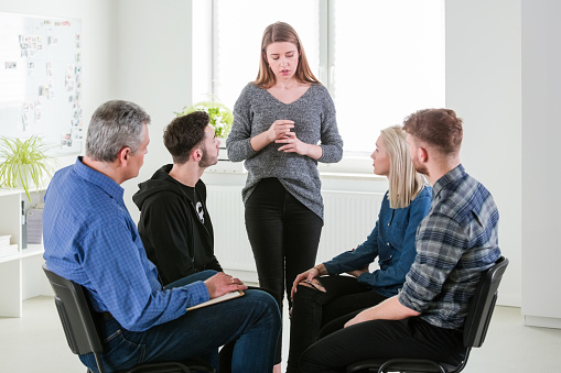 Young Woman Sharing Problems In Group Therapy Stock Photo - Download Image Now
